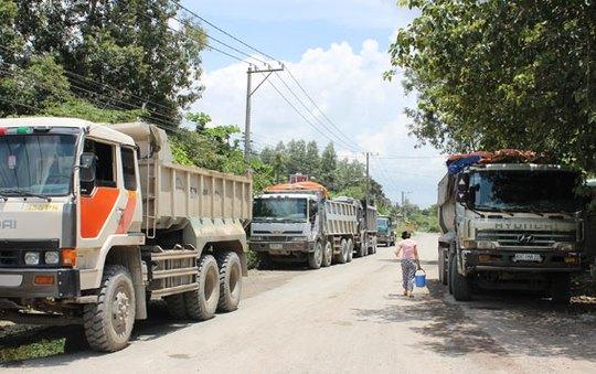 Bị người dân chặn đường hàng chục chiếc xe tải nối đuôi nhau đứng chờ.