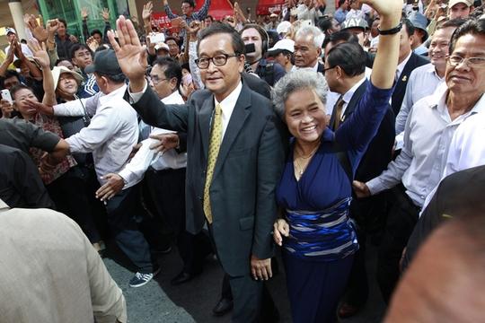 Ông Sam Rainsy, lãnh đạo Đảng CNRP, vẫy tay chào người ủng hộ bên ngoài tòa án. Ảnh: EPA