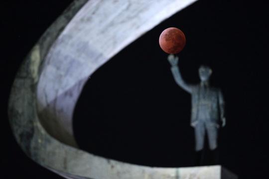 Mặt trăng nằm gọn trong tay bức tượng ở thủ đô Brasilia, Brazil. Ảnh: Reuters