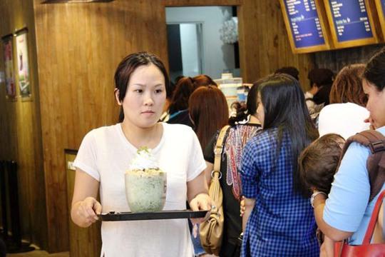 Một khách hàng đang cố gắng tìm một vị trí ngồi sau khi mua được ly cà phê khổng lồ