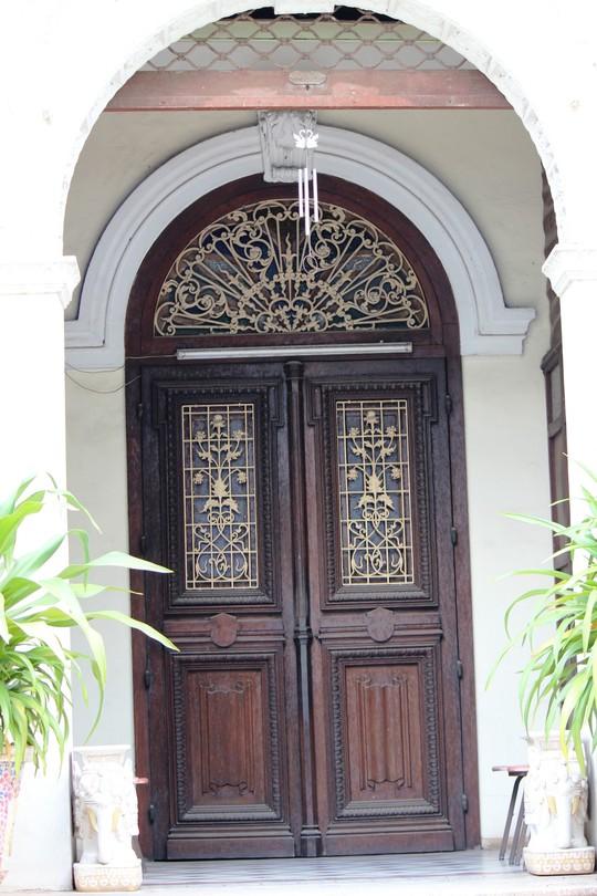 Lối vào có hai lớp cửa, bên trong của gỗ và bên ngoài của cuốn sắt được đẩy lên. Đây là một trong những nét đặc trưng kiến trúc Pháp những năm đầu thế kỉ XX