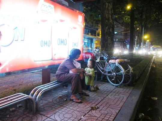 Một đứa trẻ quỳ gối, mếu máo van xin tiền người chờ xe buýt bên đường