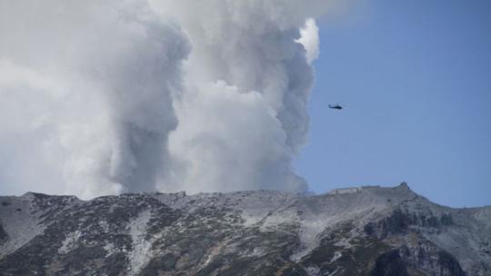 Trực thăng tham gia cứu hộ trên núi trong khi núi lửa vẫn phun bụi tro. Ảnh: AP