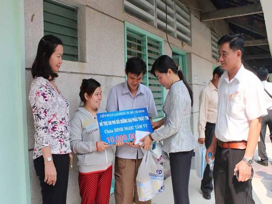 Bà Nguyễn Trần Phượng Trân, Phó Chủ tịch LĐLĐ TP (thứ hai từ phải sang), trao tiền cho gia đình anh Hiếu