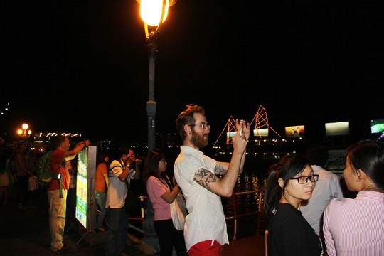 Du khách nước ngoài thích thú chụp ảnh thuyền hoa lung linh