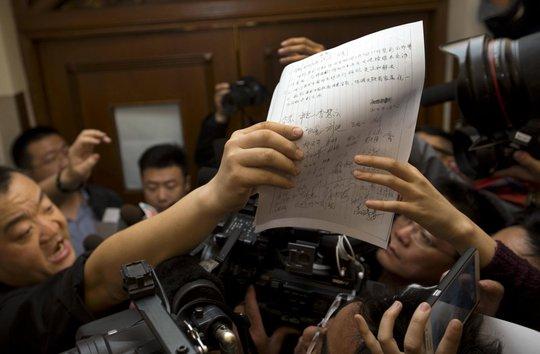 Đại diện người thân của các hàng khách Trung Quốc trên máy bay đưa lá thư. Ảnh: AP