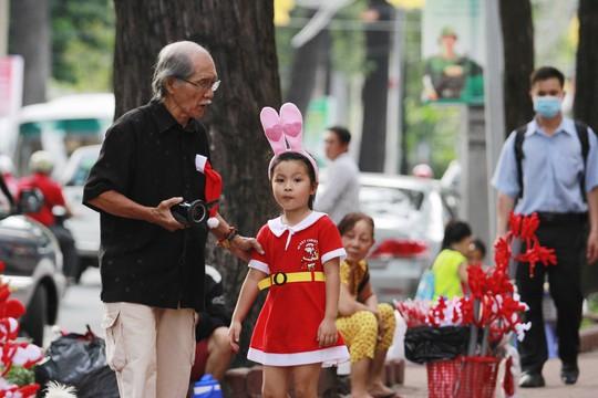 Một cụ già dẫn cháu gái trong trang phục xinh xắn đi chụp ảnh Noel