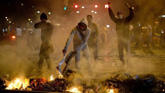 Người biểu tình đốt rác trên đường. Ảnh: AP