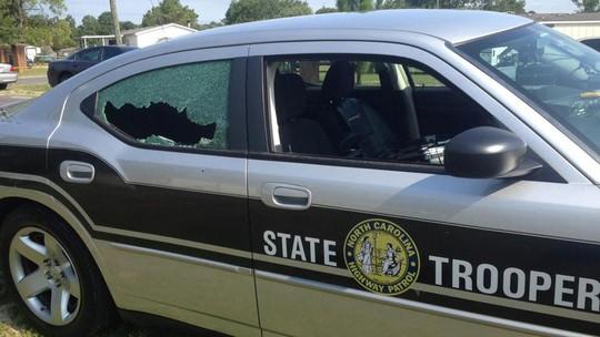 Kính xe cảnh sát bị trúng đạn trong cuộc đọ súng. Ảnh: AP