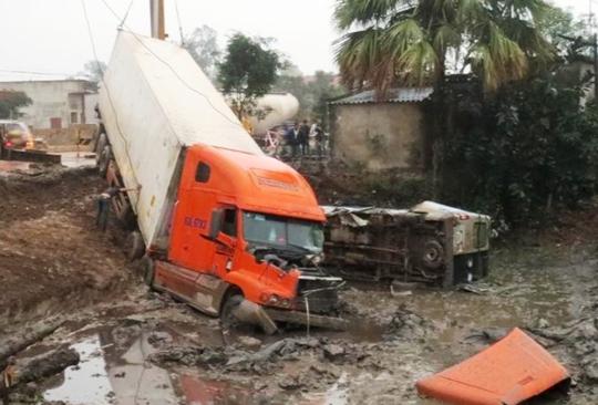 Hiện trường vụ tai nạn khiến chiếc xe ô tô 16 chỗ bị xe container đẩy xuống hố công trình, khiến 2 người chết nhiều người bị thương