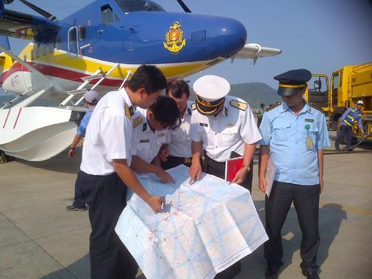 Chuẩn đô đốc Nguyễn Minh Thành (người cầm sổ đỏ) trực tiếp chỉ đạo việc tìm kiếm cho lực lượng trên chiếc thủy phi cơ DHC6 - Ảnh: Quý Lâm