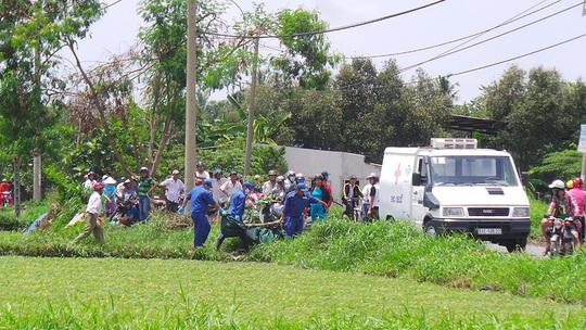 Lực lượng chức năng đưa thi thể nạn nhân ra xe để chở về nhà xác khám nghiệm tử thi vào trưa 27-5.