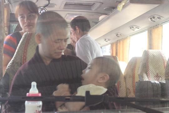 Ni sư bế một cháu bé bị tàn tật trên xe