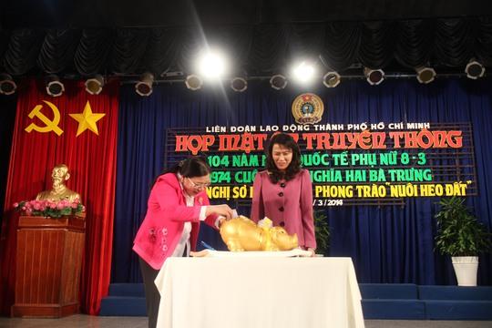 Bà Nguyễn Thị Thu, Chủ tịch LĐLĐ TP HCM và bà Nguyễn Thị Bích Thủy, Phó Chủ tịch LĐLĐ TP, mổ heo đất gây quỹ học bổng Nguyễn Đức Cảnh