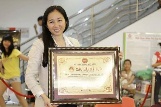 Bà Lê Minh Trang - Tổng Giám đốc Tổng Công ty Thương mại Sài Gòn (SATRA) chụp hình lưu niệm cùng  bằng xác lập kỷ lục chiếc bánh mì dài nhất Việt Nam của Siêu thị Sài Gòn