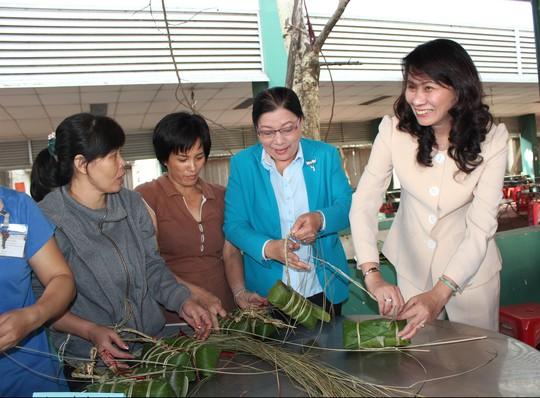 Bà Nguyễn Thị Thu, Chủ tịch LĐLĐ TP (phải) và bà Nguyễn Thị Bích Thủy, Phó Chủ tịch LĐLĐ TP (thứ hai, bên phải) gói bánh tét cùng công nhân