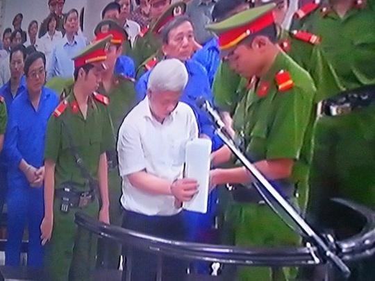 Bị cáo Nguyễn Đức Kiên được cảnh sát áp giải tháo còng trước khi nghe tòa tuyên án - Ảnh chụp qua màn hình