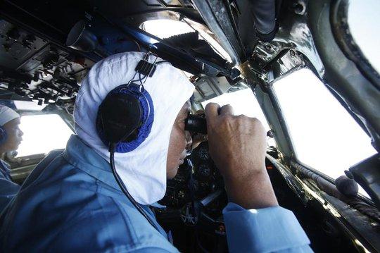 Thiếu tá Nguyễn Tri Thức, Trung đoàn Không quân 918, từ trên chiếc AN26 dùng ống nhòm tìm kiếm chiếc máy bay Malaysia mất tích - Ảnh: Reuters