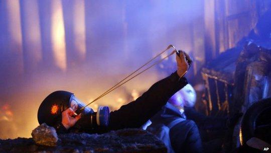 Người biểu tình bắn đá về phía cảnh sát. Ảnh: AP