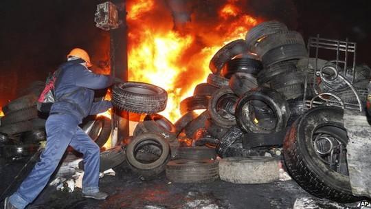Người biểu tình đốt lốp xe gần rào chắn khu vực thủ đô. Ảnh: AP