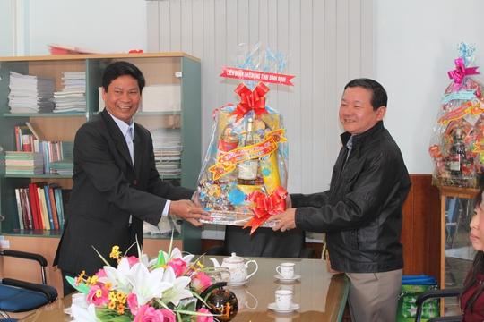Ông Huỳnh Thanh Xuân, Chủ tịch LĐLĐ tỉnh Bình Định (bìa trái), tặng quà Tết cho đại diện Công ty Môi trường Đô thị Quy Nhơn ẢNH: ANH TÚ
