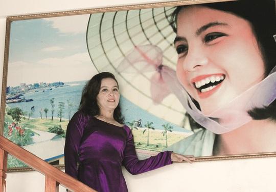 Chị Phan Thị Như Quỳnh bên bức ảnh Nụ cười Việt Nam quảng bá cho ngành du lịch. Ảnh: Q.N