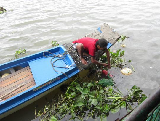 Ông Ba Chúc đang kéo thi thể nạn nhân lên bờ.