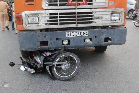 Xe máy nằm kẹt cứng dưới gầm xe container.