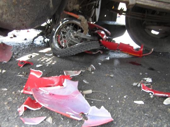 Chiếc xe máy bị cán nát dưới gầm xe đầu kéo.