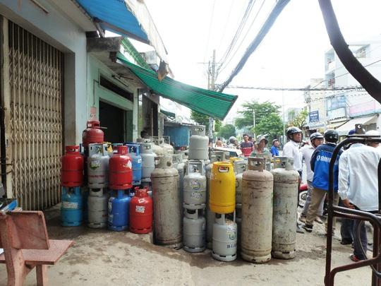 Nhờ khống chế ngọn lửa kịp thời nên may mắn các bình gas không phát nổ. Trong ảnh các bình gas được di chuyển đi nơi khác.