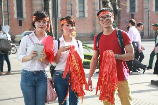 Nhiều bạn trẻ cầm cờ, đeo băng rôn đến xem trận đấu.