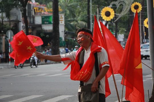 Một người bán cờ và băng rôn trên đường Phạm Ngọc Thạch.
