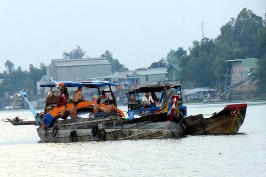 Chiếc ghe chài chở khoảng 100 tấn đường đậu sát bờ sông Hậu phía Campuchia đang sang đường cho các ghe Việt Nam để vào địa phận An Giang.