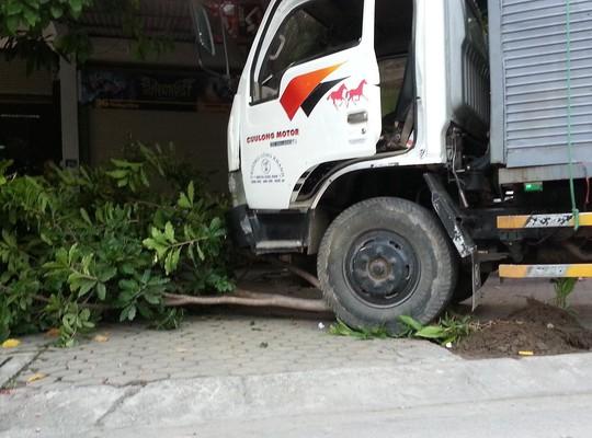 Sau khi mất lái xe tải lao lên vỉa hè đâm gãy gốc cây mới dừng lại.