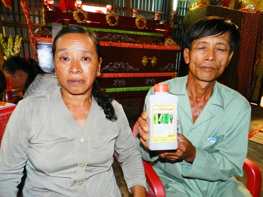 Vợ chồng ông Nguyễn Văn Tổng bên chai thuốc trừ sâu mà Kiệt dùng để tự tử