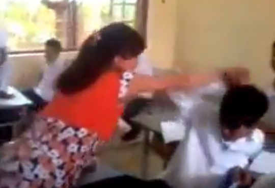 Cậu học sinh này đã phản kháng lại bằng cách liên tục đưa tay để đỡ những đòn đánh của cô giáo và cười nhạt