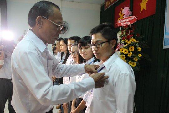 Ông Lương Văn Hồng, Chủ tịch LĐLĐ quận 3, TP HCM, gắn huy hiệu Công đoàn cho đoàn viên Công ty TNHH Apave