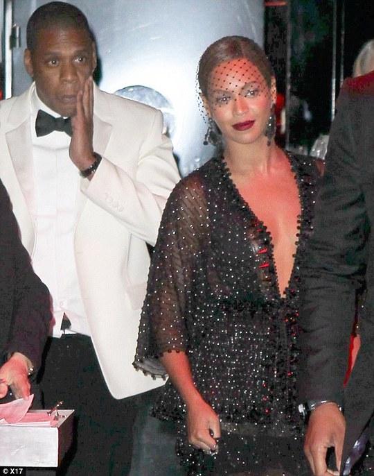 Jay Z tay ôm mặt khi rời khỏi khách sạn, trong khi Beyoncé nở nụ cười xã giao. Ảnh: X17