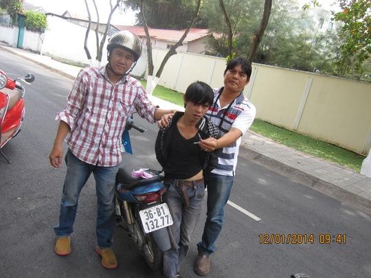 """""""Hiệp sĩ"""" Nguyễn Thanh Hải (bìa phải) cùng đồng đội Nguyễn Hoàng Bảo đang khống chế tên trộm (giữa) cùng chiếc xe tang vật."""
