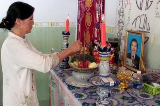 Vợ bệnh nhân Trần Đình Nam bên bàn thơ chồng.
