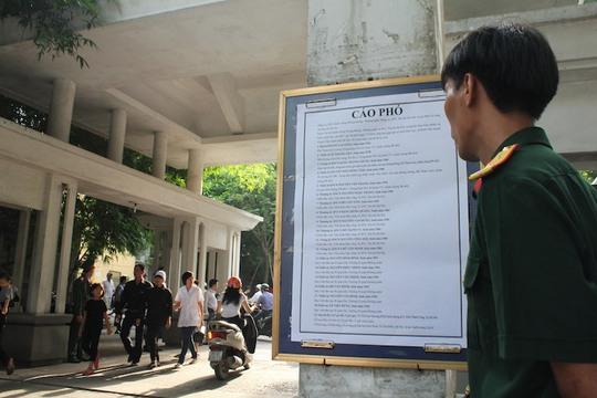 Một cán bộ đứng trước cáo phó ghi tên 18 đồng đội của mình ngoài cổng nhà tang lễ