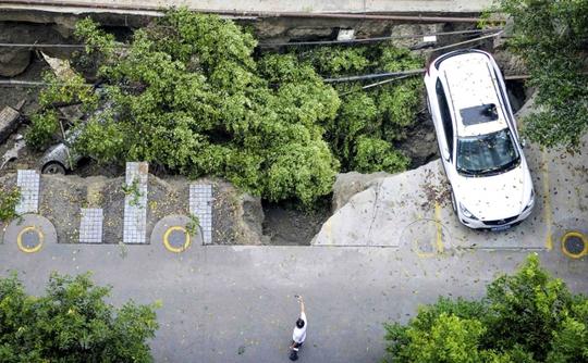 Một chiếc xe hơi đang bấp bênh trên miệng hố. Ảnh: Reuters
