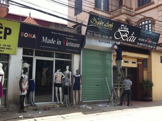 """Các cửa hàng đua nhau trưng biển """"Made in Việt Nam"""" trên dải đường dẫn vào trung tâm chợ Ninh Hiệp. Ảnh: Diệp Sa."""