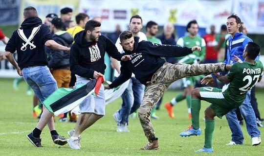Cầu thủ của Maccabi Haifa (áo xanh) bị người biểu tình đá vào ngực