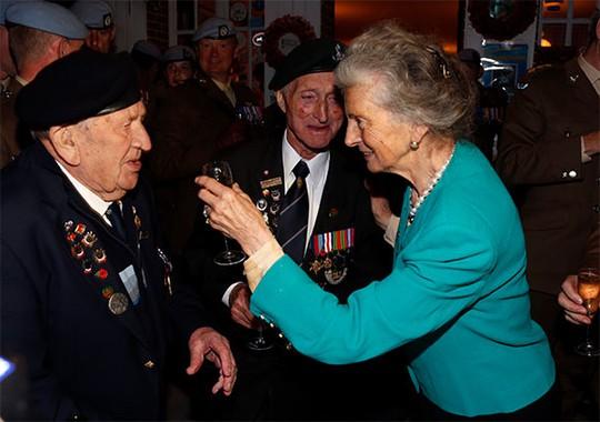 Bà Arlette Gondree, chủ tiệm cà phê trên cầu Pegasus tổ chức tiệc mừng thường niên với các cựu binh Anh ở Benouville (Pháp) hôm 5-6 nhân sự kiện D-Day. Ảnh: Reuters
