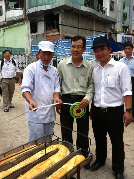 Từ phải sang: Ông Giang Minh Trường - Giám đốc Siêu thị Sài Gòn, đại diện Hội kỷ lục gia Việt Nam  và trưởng bộ phận bánh SATRA Bakery - Võ Quang Nhu kiểm tra chiều dài chiếc bánh
