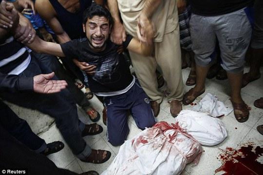 ...Một người đàn ông đau khổ cùng cực trước thi thể người thân thiệt mạng trong vụ pháo kích nhà trường. Ảnh: Reuters