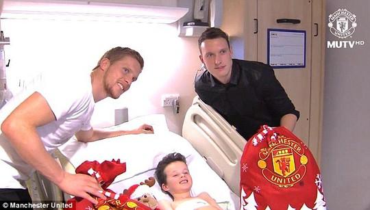 Một bệnh nhi vui cười khi được Ben Amos (trái) và Phil Jones tặng quà