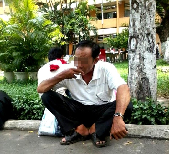 Một người đàn ông tranh thủ ngồi nghỉ bên lề công viên nhỏ giữa BV Ung bướu và tranh thủ hút luôn điếu thuốc