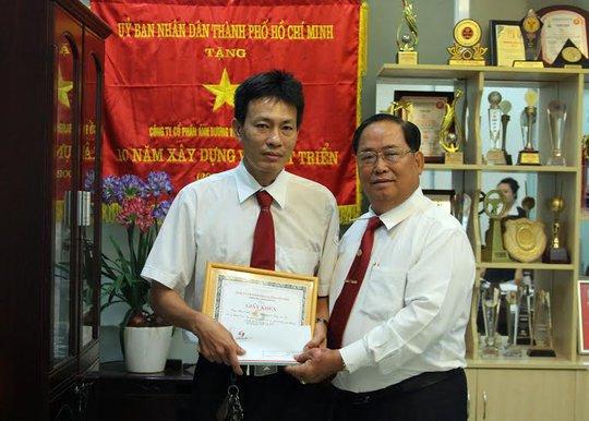 Ông Tạ Long Hỷ, Phó Tổng giám đốc Vinasun (bìa trái), trao giấy khen và tiền thưởng cho tài xế Bùi Vinh Hiển